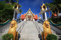 Golden lion guarding statues in thai temple against blue sky at wat sakae korat downtown thailand Royalty Free Stock Images