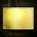 Golden metal plate on concrete wall Royalty Free Stock Photography
