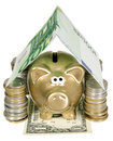 A golden moneybank under house made from banknote Royalty Free Stock Photo