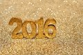 Golden 2016 new years numbers on gold background Royalty Free Stock Photo