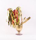 Golden party whistles with stripes, spatula and brush gathered in a golden glass