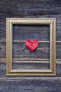 Golden picture frame on old wooden wall and heart Royalty Free Stock Photo