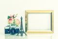 Golden picture frame, rose flowers and vintage camera. Eiffel To Royalty Free Stock Photo