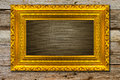 Golden picture frame with wooden background Royalty Free Stock Photos