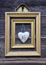 Golden picture frame on wooden wall and cloth heart Royalty Free Stock Photo