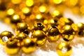 Golden plastic beads on white Royalty Free Stock Image