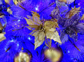 Golden poinsettia with ornaments hanging from white Christmas tr Royalty Free Stock Photo