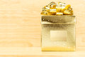 Golden present box with big bow on wooden table and wood wall, Mo Royalty Free Stock Photo