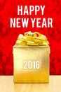 Golden Present box on wood table with Happy New Year 2016 word a Royalty Free Stock Photo