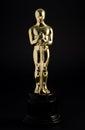 Golden replica of an oscar film award on a black background Royalty Free Stock Photo