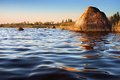 Golden rock reflecting in water on sunset baltic sea calm Stock Images