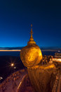 Golden rock at twilight with praying people kyaikhtiyo pagoda one of the most buddhist worship place in burma myanmar Stock Photography