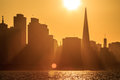 Golden san francisco skyline at sunset waterfront silhouetted shrouded by brilliant white sun in the later afternoon Royalty Free Stock Photo