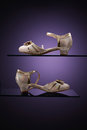 Golden shoes pair of over purple background Royalty Free Stock Images