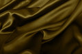Golden silk background satin texture dark wavy glossy drapery Royalty Free Stock Images