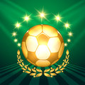 Golden soccer ball a with laurel wreath against shining stars and green background symbol of victory in competitions Stock Photo