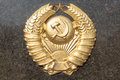 Golden soviet cccp emblem with hammer and sickle on a marble plate Royalty Free Stock Photo
