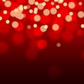 Golden sparkles on red background with bokeh effect. Royalty Free Stock Photo