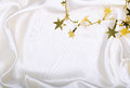 Golden stars and spangles on white silk as background Stock Images