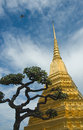 Golden stupa and a tree over blue sky background Royalty Free Stock Photo