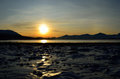 Golden sunrise over blue fjord and snowy mountain with reflection on thick ice Royalty Free Stock Photo
