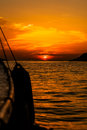 Golden sunset a beautiful sun setting on the horizon taken from a yacht with the buoy hanging off the edge Royalty Free Stock Photo