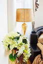 Golden vase with flowers near beautiful table lamp