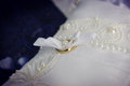 Golden wedding rings closeup pair of on silk lace pillow Royalty Free Stock Photo