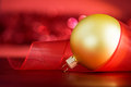 Golden xmas ball and ribbon on the red background with blurred lights Royalty Free Stock Photos