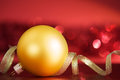 Golden xmas ball and ribbon on the red with blurred lights Royalty Free Stock Photography