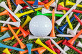 Golf ball amongst collection coloured wooden tees Royalty Free Stock Photo
