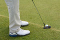 Golf ball and club on the green closeup of legs with tee grass golfer prepares to putt Royalty Free Stock Photography