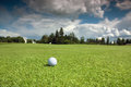 Golf ball on the course green grass blue sky and white clouds Royalty Free Stock Image