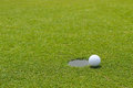 Golf ball at the edge of putting cup hold at putting green Royalty Free Stock Photo