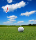 Golf ball in front of flag Royalty Free Stock Photo