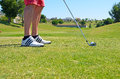 Golf ball golf shoes and stick in a green landscape Royalty Free Stock Image