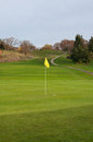 Golf ball on green fairway cart path and elevated tee box a lands next to a yellow flag the with in the background leading uphill Royalty Free Stock Images