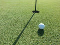 Golf ball on the green putting very close to hole Royalty Free Stock Images