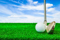 Golf ball and iron on artificial green grass Royalty Free Stock Photo