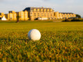 Golf ball lies in fairway of the royal and ancient st andrews course with resort and spa hotel distant background Royalty Free Stock Photo