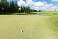 Golf ball near the hole with pole Royalty Free Stock Photo