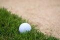 Golf ball on rough green near sand trap Stock Photos