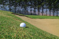 Golf ball and sand hole Royalty Free Stock Image