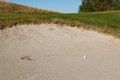 Golf ball in the sand trap a white that landed with a plop and then rolled leaving a trail a on a course Royalty Free Stock Photo