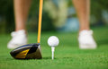 Golf ball and stick with golfer legs in background Stock Image