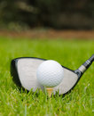 Golf ball on tee a with driver Royalty Free Stock Image