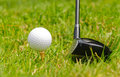 Golf ball on tee a with wood set for a left handed golfer Royalty Free Stock Photo