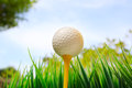 Golf ball on yellow tee and blue sky background Royalty Free Stock Photo