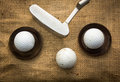 Golf balls and putter lying on metal plates next to a Royalty Free Stock Photos