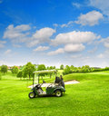 Golf cart Green course field blue sky Spring landscape Royalty Free Stock Photo